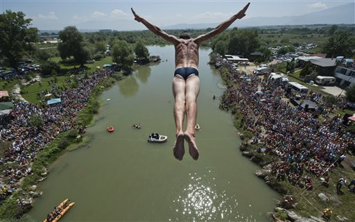 Spectators watch as a diver Sali Riza Grancina, performs the winning jump from the Ura e Shenjte bridge, Kosovo.